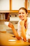 Mulher madura que guarda a xícara de café na cozinha Fotografia de Stock