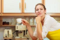 Mulher madura que guarda a xícara de café na cozinha Fotografia de Stock Royalty Free