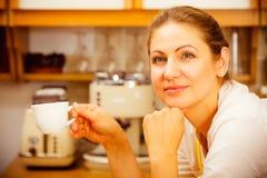 Mulher madura que guarda a xícara de café na cozinha Foto de Stock
