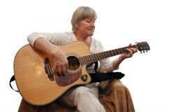 Mulher madura que joga a guitarra acústica Foto de Stock Royalty Free