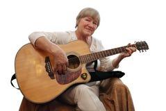 Mulher madura que joga a guitarra acústica Imagem de Stock
