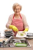 Mulher madura que limpa os pratos com uma escova imagens de stock