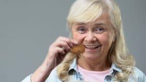 Mulher madura que mostra a cookie doce no fundo cinzento, tratamento da sobremesa da casa video estoque