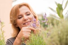 Mulher madura que olha flores imagem de stock