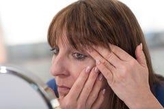 Mulher madura que olha seus enrugamentos do olho foto de stock