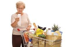 Mulher madura que olha um recibo da loja Fotografia de Stock Royalty Free