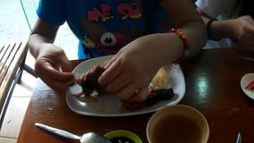 Mulher madura que rasga os pés de galinha grelhados à mão ao comer o almoço em um restaurante asiático video estoque