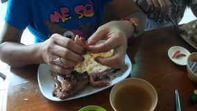 Mulher madura que rasga os pés de galinha grelhados à mão ao comer o almoço em um restaurante asiático filme