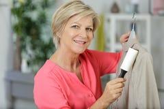 Mulher madura que remove o fluff do revestimento foto de stock royalty free