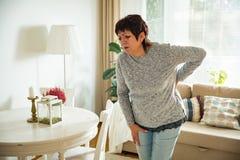 Mulher madura que sofre da dor lombar fotos de stock royalty free