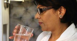 Mulher madura que toma a medicina com vidro da água 4k video estoque