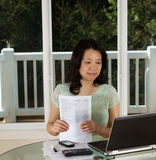 Mulher madura que trabalha em casa o escritório com formulários de imposto imagens de stock