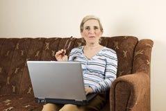 Mulher madura que usa a HOME do portátil Fotografia de Stock Royalty Free