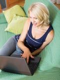 Mulher madura que usa o portátil no sofá Imagens de Stock