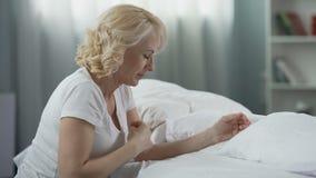 Mulher madura religiosa que senta-se perto da cama com mãos abraçadas e que reza, religião filme