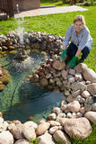 A mulher madura trabalha em torno da lagoa em seu jardim Imagem de Stock
