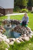A mulher madura trabalha em torno da lagoa em seu jardim Fotografia de Stock