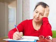 Mulher madura triste com contas de serviço público Imagem de Stock
