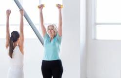 Mulher magro atlética que mantém pesos pequenos Imagem de Stock Royalty Free