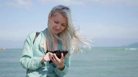 Mulher magro bonita com cabelo louro longo e a camisa verde que estão e que usam o smartphone sobre o mar do fundo Menina video estoque