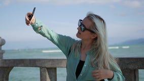 Mulher magro bonita com cabelo louro longo nos óculos de sol e na camisa verde que estão a palmeira próxima e que fazem o selfie  video estoque