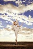 A mulher magro bonita nova pratica a ioga na praia em sunris Fotografia de Stock