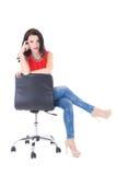 Mulher magro bonita nova que senta-se na cadeira do escritório isolada em w Foto de Stock Royalty Free