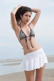 A mulher magro com o corpo bonito que veste a mini saia e o sutiã levantam na praia imagens de stock