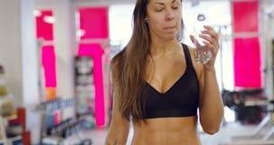 A mulher magro de sorriso com corpo do ajuste bebe a água no gym da aptidão vídeos de arquivo