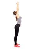 Mulher magro e apta nova que estica para trás com os braços aumentados acima Fotografia de Stock Royalty Free