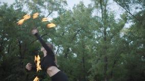 Mulher magro na dança da máscara, executando uma mostra com a bola de fogo que está no riverbank Exibição hábil do artista do fir video estoque