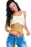 Mulher magro nas calças de brim com medida de fita Fotos de Stock