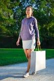 Mulher magro nova feliz no sportswear que anda no parque com shoppi fotografia de stock