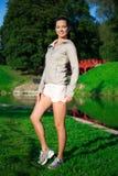 Mulher magro nova no sportswear que está no parque fotos de stock royalty free