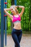 A mulher magro nova ostenta o retrato no campo de treino Foto de Stock