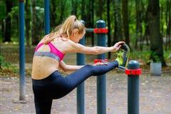 Mulher magro nova que estica em um campo de treino Fotografia de Stock