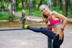Mulher magro nova que estica em um campo de treino Fotos de Stock Royalty Free