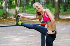 Mulher magro nova que estica em um campo de treino Fotos de Stock