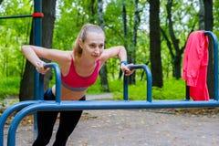Mulher magro nova que faz o exercício em um campo de treino Imagens de Stock Royalty Free