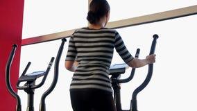 Mulher magro que exercita no instrutor elíptico no clube de aptidão para manter o ajuste do corpo filme