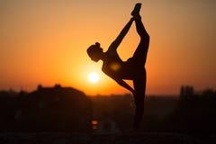 Mulher magro que faz a ioga sobre o sol alaranjado Fotografia de Stock