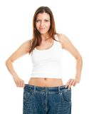 Mulher magro que puxa calças de brim desproporcionados Foto de Stock