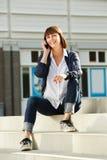 Mulher mais idosa alegre que senta-se em etapas com telefone esperto imagem de stock
