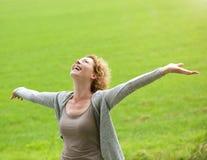 Mulher mais idosa alegre que sorri com os braços estendido Fotografia de Stock