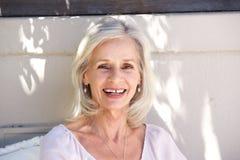 Mulher mais idosa bonita que sorri e que olha a parte externa segura foto de stock royalty free