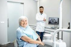 Mulher mais idosa com o dentista no escritório dental fotografia de stock