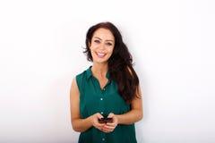 Mulher mais idosa de sorriso com o telefone esperto contra o fundo branco foto de stock royalty free