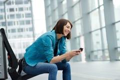 Mulher mais idosa de sorriso que senta-se com telefone celular Fotos de Stock Royalty Free