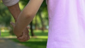 Mulher mais idosa que guarda as mãos com seu neto e que anda no parque do verão, fim de semana video estoque