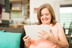 Mulher mais idosa que tem o divertimento com tecnologia imagens de stock